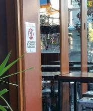 "sign outside of commercial hotel, saying ""no smoking in this area"""